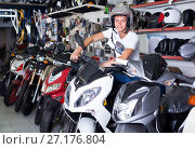 Купить «Portrait of glad male in helmet on motorbike in the store», фото № 27176804, снято 17 июля 2017 г. (c) Яков Филимонов / Фотобанк Лори