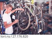 Купить «Adult male is checking tire on wheel», фото № 27176820, снято 17 июля 2017 г. (c) Яков Филимонов / Фотобанк Лори