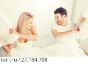 Купить «happy couple having pillow fight in bed at home», фото № 27184708, снято 25 февраля 2016 г. (c) Syda Productions / Фотобанк Лори