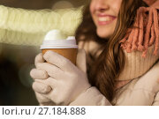 Купить «happy woman with coffee over christmas lights», фото № 27184888, снято 2 декабря 2016 г. (c) Syda Productions / Фотобанк Лори