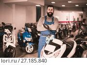 Купить «cheerful man worker displaying various motorcycles in workshop», фото № 27185840, снято 21 сентября 2019 г. (c) Яков Филимонов / Фотобанк Лори