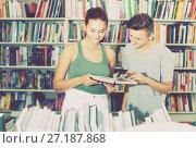 Купить «Two interested teenagers reading book together», фото № 27187868, снято 16 сентября 2016 г. (c) Яков Филимонов / Фотобанк Лори
