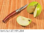 Купить «Разрезанное зеленое яблоко с ножом на бамбуковой циновке», фото № 27191264, снято 7 ноября 2017 г. (c) Сергей Васильев / Фотобанк Лори