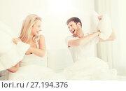 Купить «happy couple having pillow fight in bed at home», фото № 27194376, снято 25 февраля 2016 г. (c) Syda Productions / Фотобанк Лори