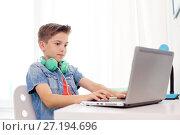 Купить «happy boy with headphones typing on laptop at home», фото № 27194696, снято 10 июня 2017 г. (c) Syda Productions / Фотобанк Лори