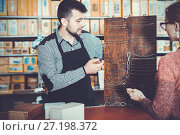 Купить «Seller assisting woman in choosing door hinges», фото № 27198372, снято 5 апреля 2017 г. (c) Яков Филимонов / Фотобанк Лори