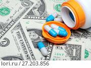 Купить «Баночка из-под лекарств с капсулами, рассыпанными на американских долларах», фото № 27203856, снято 10 декабря 2011 г. (c) Александр Гаценко / Фотобанк Лори