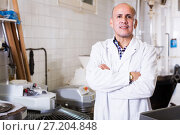 Купить «Worker standing near table in manufacture», фото № 27204848, снято 22 апреля 2017 г. (c) Яков Филимонов / Фотобанк Лори