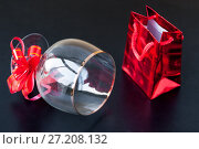 Купить «Red gift bag and glass with bow on black background», фото № 27208132, снято 28 октября 2017 г. (c) Катерина Белякина / Фотобанк Лори