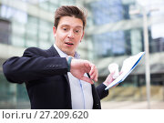 Купить «Businessman hurrying to meeting and watching on wristwatch», фото № 27209620, снято 20 апреля 2017 г. (c) Яков Филимонов / Фотобанк Лори
