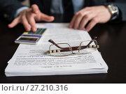 Купить «Мужчина считает на калькуляторе. Очки лежат на документах. Фокус на очках», эксклюзивное фото № 27210316, снято 6 ноября 2017 г. (c) Игорь Низов / Фотобанк Лори