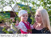 Купить «Mom with a small child in the background of giving», фото № 27210640, снято 11 июня 2017 г. (c) Катерина Белякина / Фотобанк Лори