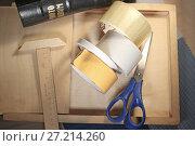 Купить «Натюрморт на канцелярскую тему. Ножницы, скотч, линейка лежат на деревянной поверхности.», фото № 27214260, снято 18 ноября 2017 г. (c) Юлия Юриева / Фотобанк Лори