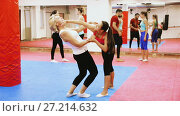 Купить «Young woman is doing self-defence moves with coach in sporty gym.», видеоролик № 27214632, снято 22 октября 2017 г. (c) Яков Филимонов / Фотобанк Лори