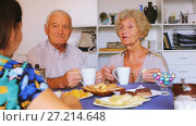Купить «Smiling elderly spouses enjoying time with young girl at home, drinking tea with sweets», видеоролик № 27214648, снято 7 сентября 2017 г. (c) Яков Филимонов / Фотобанк Лори