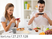 Купить «couple with smartphones having breakfast at home», фото № 27217128, снято 19 октября 2017 г. (c) Syda Productions / Фотобанк Лори