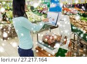 Купить «customer weighing apples on scale at grocery store», фото № 27217164, снято 2 ноября 2016 г. (c) Syda Productions / Фотобанк Лори