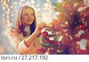 Купить «happy young woman decorating christmas tree», фото № 27217192, снято 15 октября 2016 г. (c) Syda Productions / Фотобанк Лори