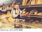 Купить «Male shop assistant demonstrating delicious loaves of bread in bakery», фото № 27219908, снято 26 января 2017 г. (c) Яков Филимонов / Фотобанк Лори