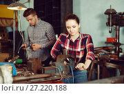 Купить «Portrait of adult female working near vise», фото № 27220188, снято 10 октября 2017 г. (c) Яков Филимонов / Фотобанк Лори