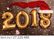 Купить «Bright metallic gold balloons figures 2018, Christmas, New Year Balloon with glitter stars on dark wood table background», фото № 27220488, снято 19 ноября 2017 г. (c) Сергей Тимофеев / Фотобанк Лори