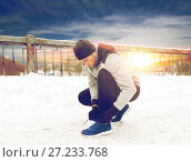 Купить «man with earphones tying sports shoes in winter», фото № 27233768, снято 10 ноября 2016 г. (c) Syda Productions / Фотобанк Лори