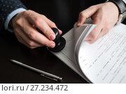 Купить «Мужчина ставит печать на документах», эксклюзивное фото № 27234472, снято 6 ноября 2017 г. (c) Игорь Низов / Фотобанк Лори