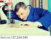 Купить «Man operating automatic screwdriver in wood workshop», фото № 27234540, снято 19 января 2019 г. (c) Яков Филимонов / Фотобанк Лори