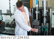 Купить «Professional conveyor worker checking quality of bottles», фото № 27234632, снято 22 сентября 2016 г. (c) Яков Филимонов / Фотобанк Лори