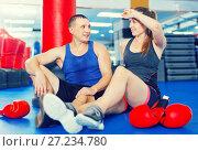 Купить «Female boxer is sitting with man and talking about healthy in gym.», фото № 27234780, снято 21 августа 2017 г. (c) Яков Филимонов / Фотобанк Лори