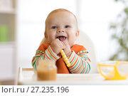 Купить «Happy infant baby boy spoon eats itself», фото № 27235196, снято 24 ноября 2017 г. (c) Оксана Кузьмина / Фотобанк Лори