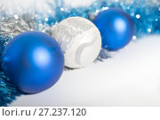 Купить «Christmas decorations of blue and silver on a white background - three balls and a tinsel», фото № 27237120, снято 24 ноября 2017 г. (c) Юлия Бабкина / Фотобанк Лори