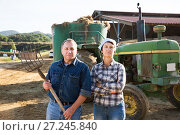 Купить «senior man and woman owners of farm standing near tractor», фото № 27245840, снято 24 октября 2017 г. (c) Яков Филимонов / Фотобанк Лори