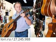 Купить «Mature man choosing acoustic guitar», фото № 27245988, снято 18 сентября 2017 г. (c) Яков Филимонов / Фотобанк Лори