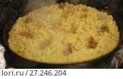 Купить «Cooking pilaf, shef makes holes for the boiling of the pilaf in cast-iron kettle», видеоролик № 27246204, снято 2 октября 2017 г. (c) Ирина Мойсеева / Фотобанк Лори