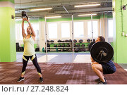 Купить «man and woman with weights exercising in gym», фото № 27248824, снято 19 февраля 2017 г. (c) Syda Productions / Фотобанк Лори