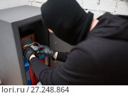 Купить «thief stealing valuables from safe at crime scene», фото № 27248864, снято 5 мая 2017 г. (c) Syda Productions / Фотобанк Лори