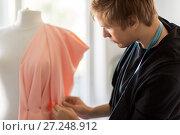 Купить «fashion designer with dummy making dress at studio», фото № 27248912, снято 28 июня 2017 г. (c) Syda Productions / Фотобанк Лори