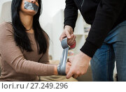 Купить «criminal tying woman with adhesive tape», фото № 27249296, снято 5 мая 2017 г. (c) Syda Productions / Фотобанк Лори