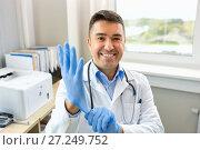 Купить «smiling doctor with protective gloves at clinic», фото № 27249752, снято 6 октября 2017 г. (c) Syda Productions / Фотобанк Лори