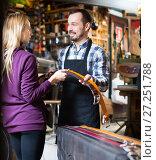 Купить «Young man worker assisting female customer in choosing belt», фото № 27251788, снято 21 августа 2019 г. (c) Яков Филимонов / Фотобанк Лори
