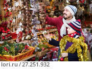 Купить «Smiling man with small girl choosing decorations», фото № 27251932, снято 21 сентября 2018 г. (c) Яков Филимонов / Фотобанк Лори