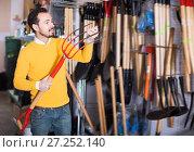 Купить «Cheerful man choosing new pitchfork», фото № 27252140, снято 2 марта 2017 г. (c) Яков Филимонов / Фотобанк Лори