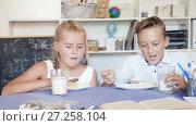 Купить «Girl and boy are eating at lunch time.», видеоролик № 27258104, снято 11 августа 2017 г. (c) Яков Филимонов / Фотобанк Лори