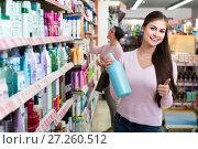 Купить «woman picking bottles with shampoo and conditioner from shelf in cosmetics store», фото № 27260512, снято 11 декабря 2017 г. (c) Яков Филимонов / Фотобанк Лори