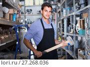 Купить «Portrait of male in uniform who is standing with sledgehammer», фото № 27268036, снято 26 июля 2017 г. (c) Яков Филимонов / Фотобанк Лори