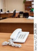 Купить «Белый кнопочный телефон на столе в офисе», фото № 27268380, снято 29 июня 2011 г. (c) Кекяляйнен Андрей / Фотобанк Лори