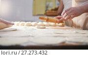 Купить «Cooks roll the dough for baking, pieces of raw dough on the wooden Board», видеоролик № 27273432, снято 27 июня 2019 г. (c) Константин Шишкин / Фотобанк Лори