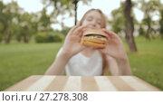 Купить «A student girl takes a cooked hamburger with her hands. She eats it in the open air. Summer. Recreation.», видеоролик № 27278308, снято 20 октября 2017 г. (c) Mikhail Davidovich / Фотобанк Лори