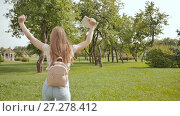 Купить «A young girl-student with a backpack on her back and notes in her hands is walking in the park. Rest during study.», видеоролик № 27278412, снято 20 октября 2017 г. (c) Mikhail Davidovich / Фотобанк Лори